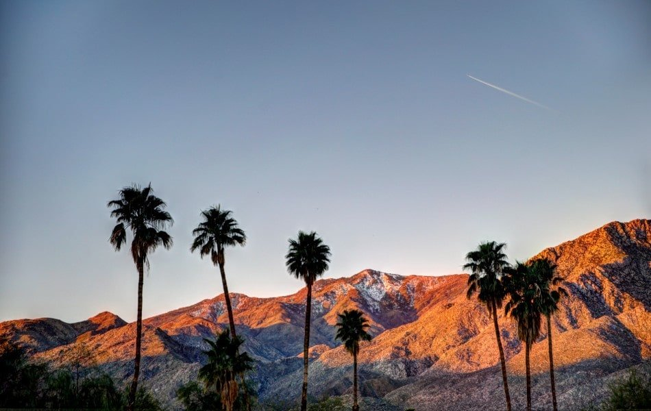 Sunset over Coachella Valley mountains and palm trees